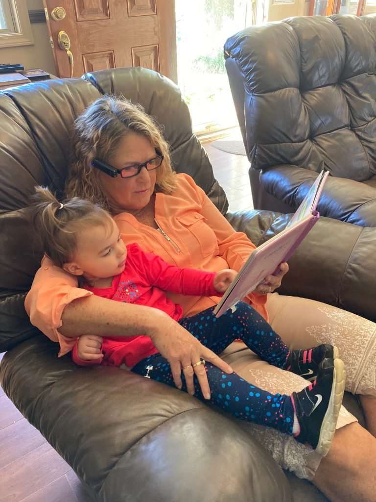 Picture of Teresa reading to her grand daughter.