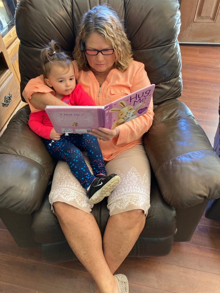Picture of Teresa reading to her grand daughter using her new MyEye